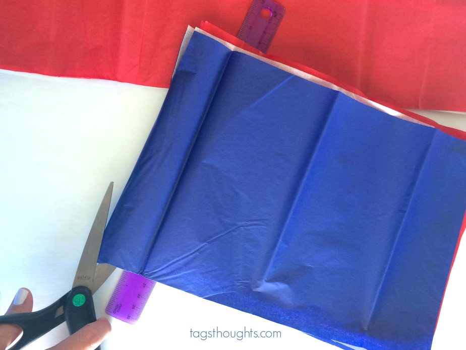 Scissors and blue tissue paper used for creating tissue sparklers.