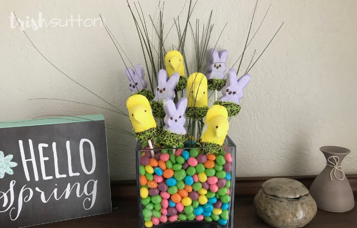 Create a festive and Edible Easter Centerpiece with Peeps, Chocolate Chips & Jelly Beans. This Chocolate Dipped Peeps Bouquet is as sweet as it is colorful.TrishSutton.com